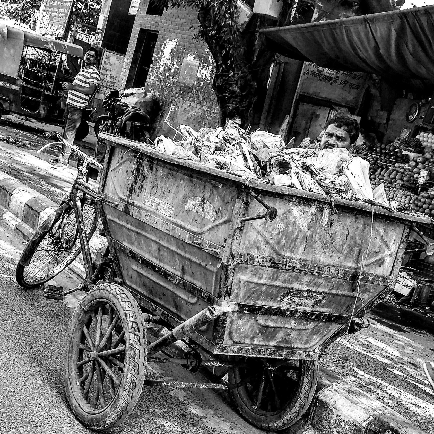 A road-cleaner uploading waste on his van in the Green Park area of South Delhi