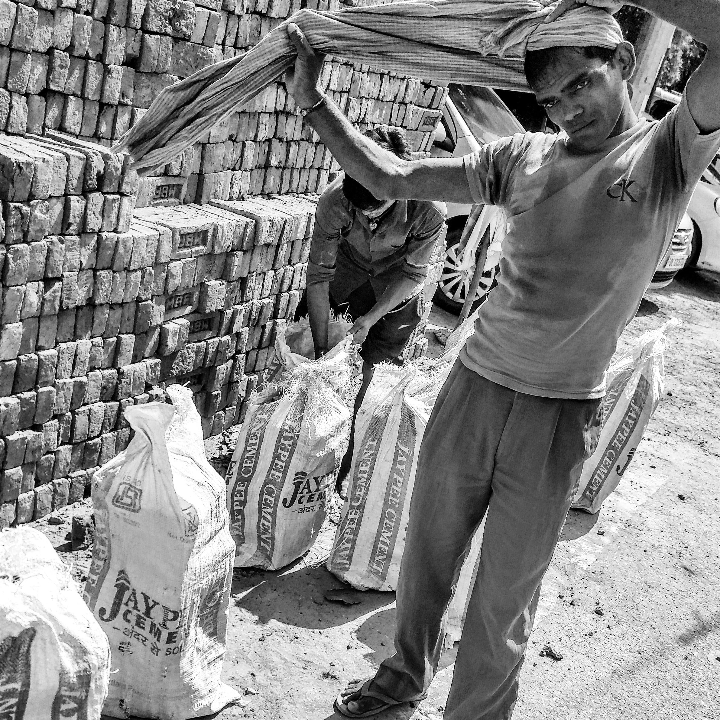 A daily wage worker tying a piece of cloth on his head before he picks up the bags filled with bricks