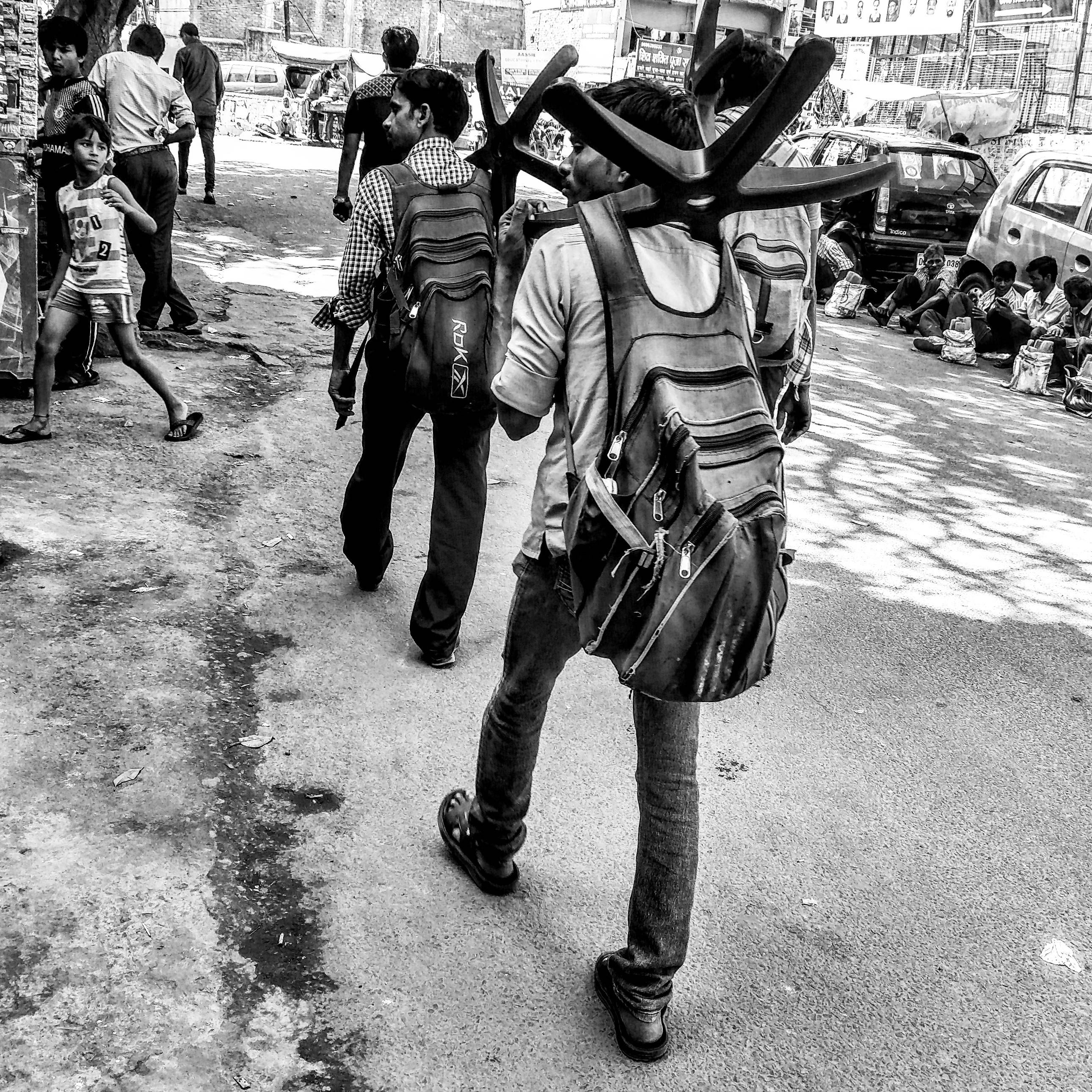 A boy looks on as a group of repair men with chair-wheels placed on their shoulders walk by.