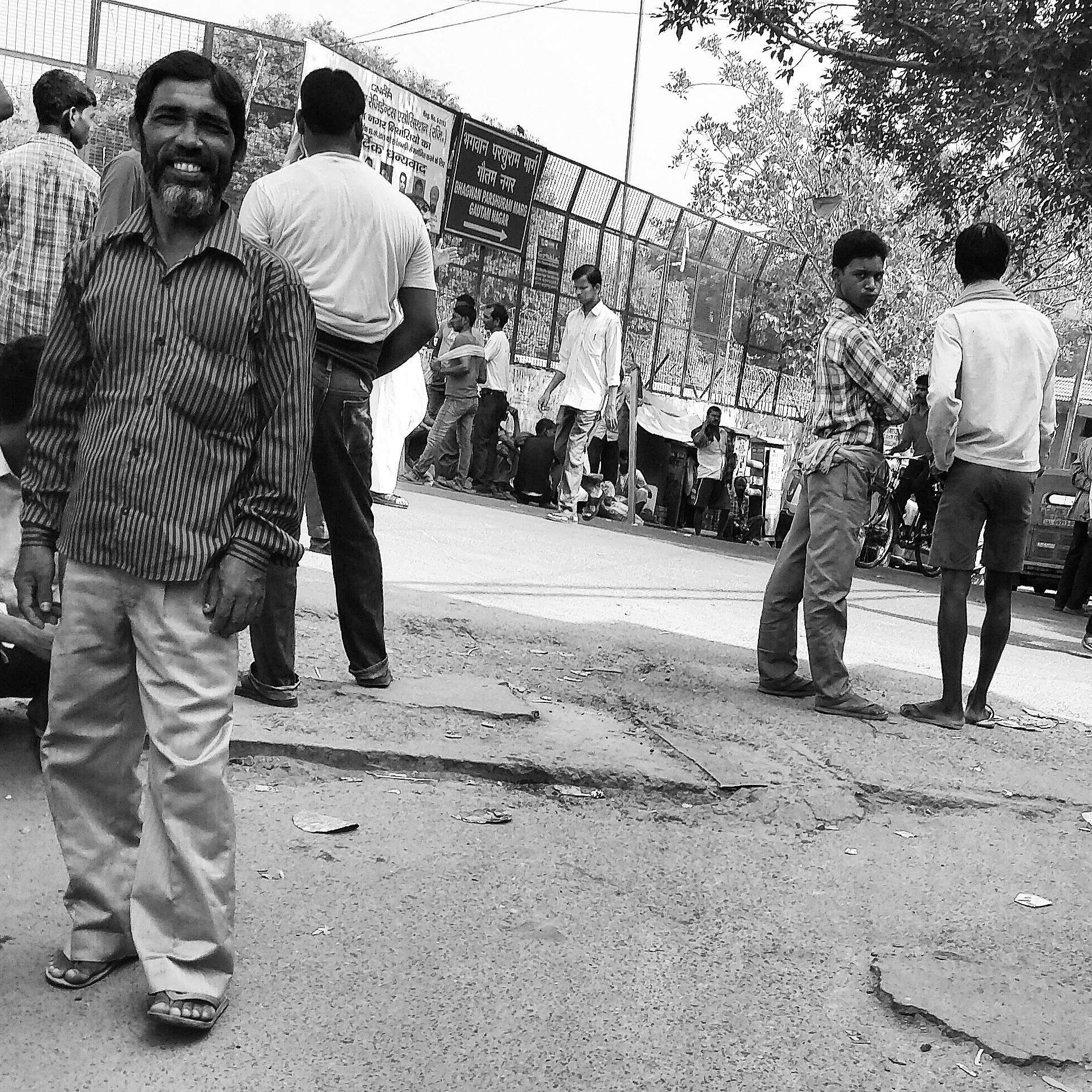 Daily wage labourers looks on while waiting to get picked up by prospective clients.