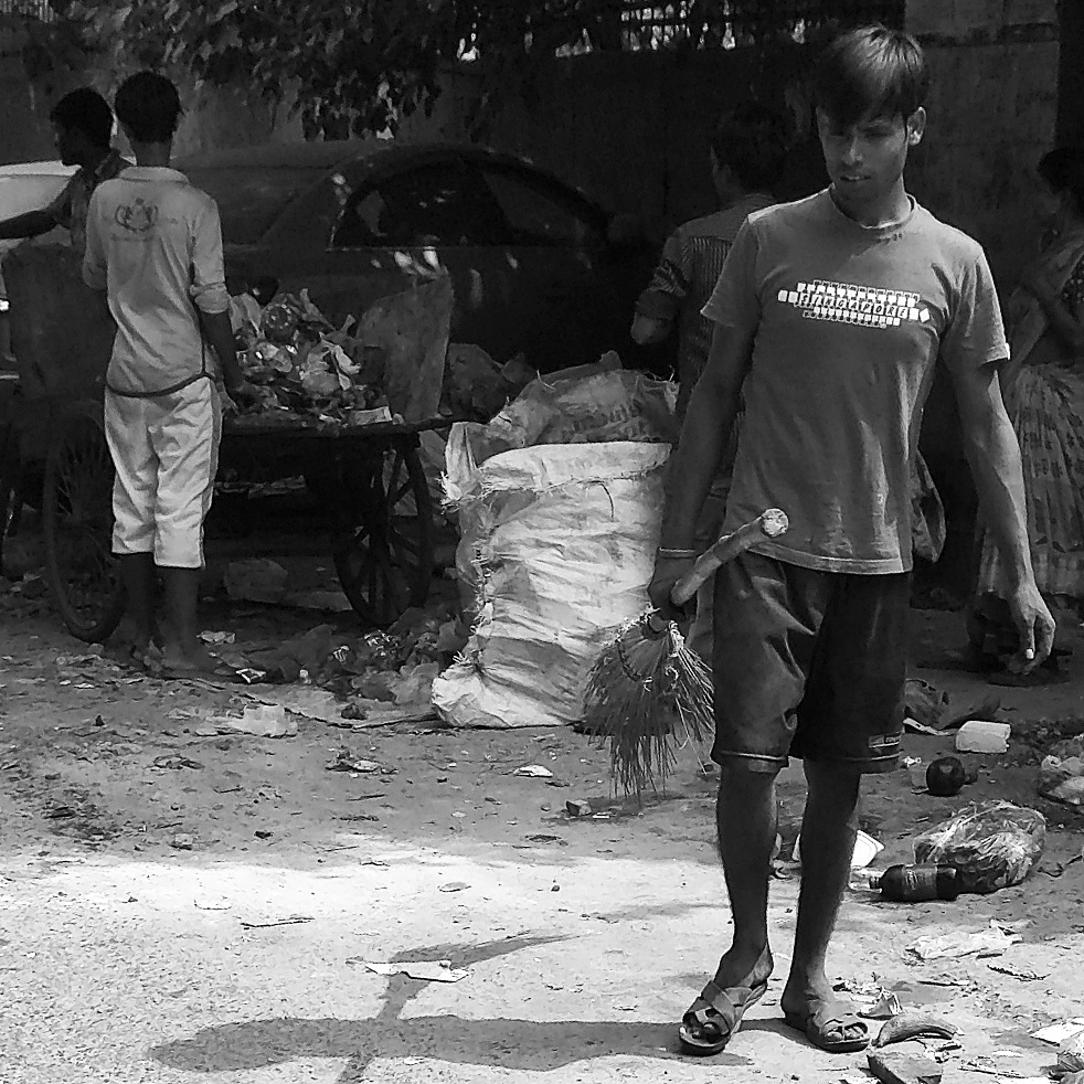 Two cleaners upload waste on their van as another cleaner with a broom on his hand looks on