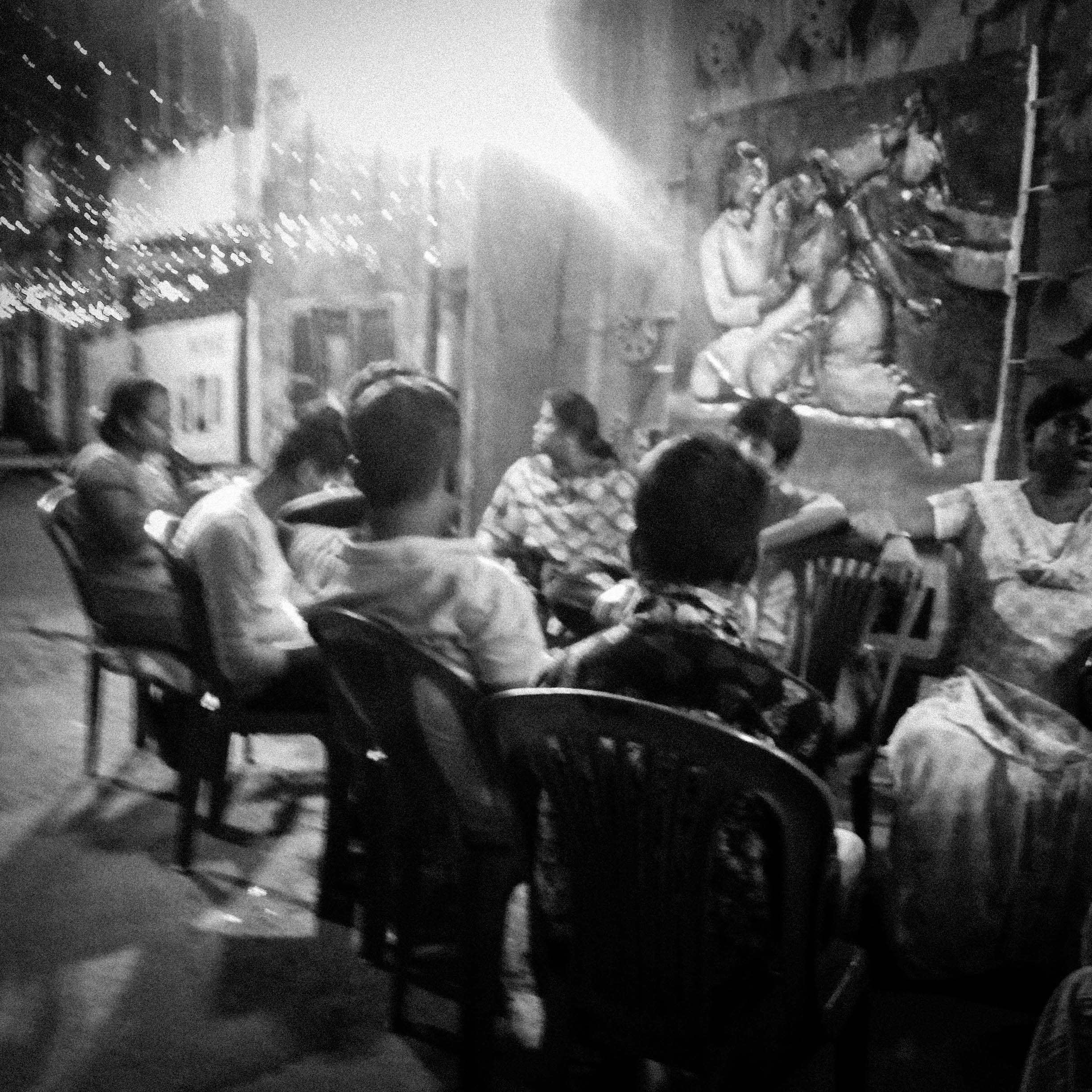 Well past midnight, as we walk around the art panels and chat, members of the community are warm and relaxed. They admire our clothes, gazing keenly and dispensing friendly smiles while trying to gauge the tenor of our interest. The ambience in this pandal stands them apart from most community puja pandals one may walk through in the city; we remark on this as they give us directions to another puja in the neighbourhood we want to visit, and cheerfully quarrel among themselves about the shorter route there with less kharap lok (bad people).