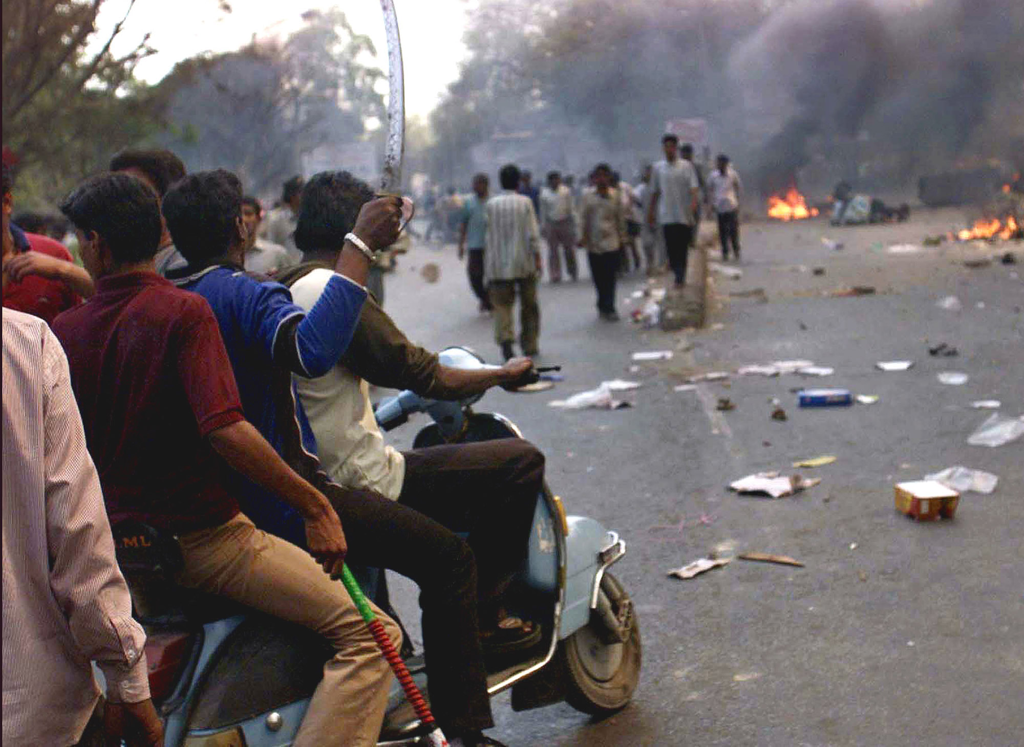 Youths with swords and sticks ride through a street of Ahmadabad, India Thursday, Feb. 28, 2002, a day after a Muslim mob attacked a train, killing 58 people in the Indian state of Gujarat. The city of Ahmadabad was besieged by violence on Thursday to avenge the attack. (AP Photo/Manish Swarup)